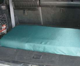 A foam dog bed for an SUV with a plywood base, covered with a discarded curtain