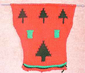 A light and dark green Christmas dog sweater with pictures of Christmas trees and gifts.